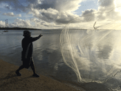 A traditional fisherman throws his net outside the workshop venue.