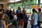 Approximately 19 people stand around a room with large windows. They are all looking toward the windows where different colored post it notes are being placed up in loose columns. Some people are holding post it notes as they wait to put theirs on the win